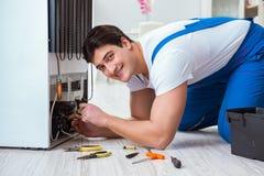 L'entrepreneur de dépanneur réparant le réfrigérateur dans le concept diy Photos stock