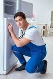 L'entrepreneur de dépanneur réparant le réfrigérateur dans le concept diy Images libres de droits