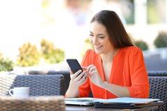 L'entrepreneur heureux utilise un t?l?phone intelligent dans une terrasse de barre image stock