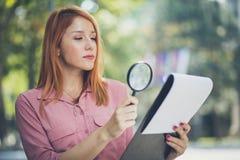 L'entrepreneur observe des diagrammes avec la loupe photo stock
