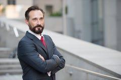 L'entrepreneur positif regardant loin avec des bras a croisé photographie stock libre de droits