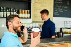L'entrepreneur sûr choisissent la boisson dans la tasse de papier pour aller tandis que communiquez le mobile L'homme parlent le  photos stock