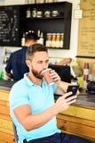 L'entrepreneur sûr choisissent la boisson dans la tasse de papier pour aller tandis que communiquez le mobile Internet d'homme et images stock