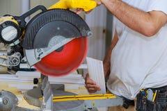 L'entrepreneur utilisant la circulaire a vu couper la plinthe neuve pour la rénovation photo stock
