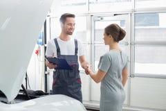 L'entretien de sourire machinent serrer la main au client féminin dans l'atelier de réparations de voiture Image stock