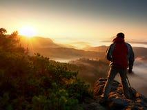 L'entusiasta felice della foto gode della fotografia dell'alba di caduta in natura sulla scogliera immagine stock