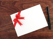 L'enveloppe blanche de la carte de voeux d'invitation ou avec le double rouge simple de ruban a attaché l'arc et le stylo noir su photographie stock libre de droits