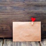 L'enveloppe de l'agrafe de papier d'emballage sous forme de coeur sur un fond en bois, jour du ` s de Valentine, attitudes du ` s Photo libre de droits