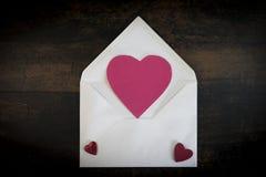 L'enveloppe de lettre d'amour avec la main rouge de coeur a ouvré la lettre d'amour avec le chiffre en forme de coeur de papier r Images stock