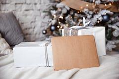 L'enveloppe de Papier d'emballage se trouve sur le lit contre le l'arbre de Noël images stock