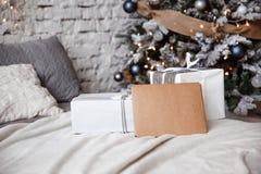 L'enveloppe de Papier d'emballage se trouve sur le lit contre le l'arbre de Noël images libres de droits