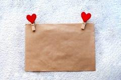 L'enveloppe du papier d'emballage avec deux pinces à linge rouges sous forme de coeurs, jour du ` s de Valentine, attitudes du `  Images libres de droits