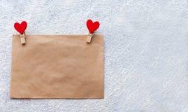 L'enveloppe du papier d'emballage avec deux pinces à linge rouges sous forme de coeurs, jour du ` s de Valentine, attitudes du `  Photos libres de droits