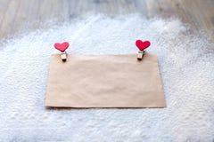 L'enveloppe du papier d'emballage avec deux pinces à linge rouges sous forme de coeurs, jour du ` s de Valentine, attitudes du `  Photos stock