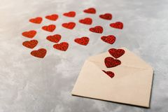 L'enveloppe du papier de métier avec les coeurs rouges amassent la diffusion sur le fond gris Photographie stock libre de droits