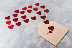 L'enveloppe du papier de métier avec les coeurs rouges amassent la diffusion sur le fond gris Photos stock