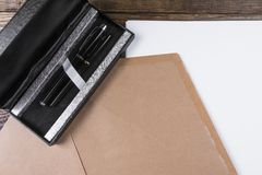 L'enveloppe est sur la feuille de papier sur la table en bois de vintage Est après un ensemble avec deux poignées photos libres de droits