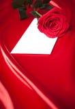 L'enveloppe et le rouge se sont levés au-dessus du fond en soie Photographie stock libre de droits