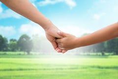 L'environnement chaud pour des parents et des enfants sur le fond brouillé nature Bébé de main de mère Photographie stock