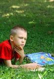 l'erba del ragazzo legge il manuale di seduta immagine stock