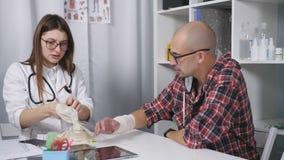 L'esame del paziente nell'ambulatorio con un polso danneggiato il medico esamina i raggi x del paziente video d archivio