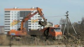 L'escavatore arancio carica l'argilla nell'autocarro con cassone ribaltabile stock footage