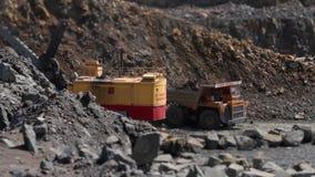 L'escavatore carica una pietra nel camion pesante nel granito di estrazione mineraria della cava archivi video