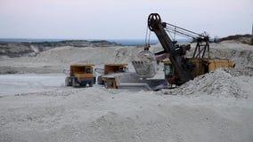 L'escavatore carica una roccia del camion nella cava video d archivio
