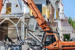 L'escavatore con le mandibole idrauliche funziona al cantiere di demolizione Fotografia Stock Libera da Diritti
