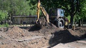 L'escavatore a cucchiaia rovescia accatasta sul primo piano a terra stock footage