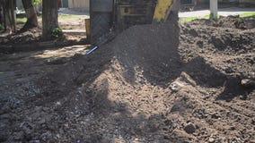 L'escavatore a cucchiaia rovescia accatasta sul primo piano a terra r stock footage