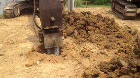 L'escavatore a cucchiaia rovescia con un acciaio del martello accatasta il dispositivo alla fondazione su pali del cantiere archivi video