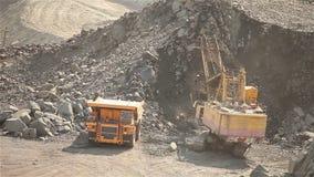 L'escavatore e lo scaricatore nella cava, escavatore carica le materie prime nello scaricatore, lavoro nella cava del minerale di stock footage