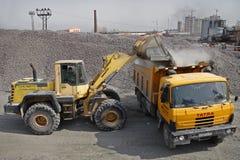 L'escavatore giallo carica la ghiaia nel ribaltatore arancio dell'autocarro con cassone ribaltabile Immagini Stock Libere da Diritti