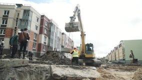 L'escavatore giallo si abbassa sull'anello concreto della botola delle catene al cantiere stock footage