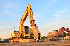 L'escavatore su un cantiere taglia e si sbriciola il vecchi calcestruzzo ed asfalto Smerigliatrice idraulica dell'interruttore fotografia stock