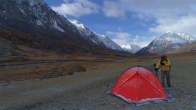 L'escursione del supporto dell'uomo sta venendo alla tenda sui precedenti della montagna 4K aereo archivi video