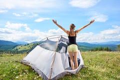 L'escursione turistica della donna nella traccia di montagna, godente della mattina soleggiata dell'estate in montagne si avvicin immagine stock libera da diritti