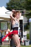 L'esecutore di circo fa il cerchio di Hula al festival di sorgente Fotografia Stock