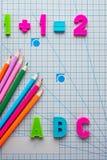 L'esempio matematico e le lettere latine inglesi dell'alfabeto hanno colorato le matite Fotografia Stock