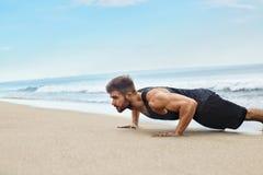 L'esercitazione dell'uomo, facente spinge verso l'alto gli esercizi sulla spiaggia Allenamento di forma fisica Immagini Stock Libere da Diritti