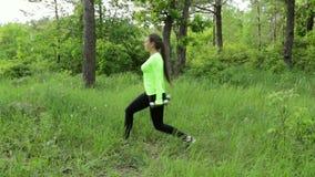 L'esercitazione della giovane donna, facente si accovaccia con i dumbbels in parco archivi video