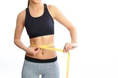 L'esercizio della ragazza nel modo sportivo e nel controllo muscles dopo addestramento di forma fisica Fotografie Stock Libere da Diritti