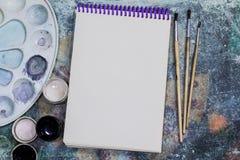 L'espace créatif L'espace de fonctionnement de l'artiste sur la table minable : peignez la gouache, carnet, brosses image stock