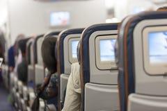 L'espace d'allocation des places avec des multimédia examine la carlingue d'avion de classe touriste images stock