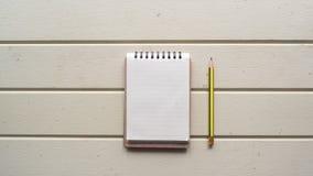 L'espace de fonctionnement, carnet, avec le crayon sur le bureau en bois blanc Image libre de droits
