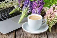 L'espace de fonctionnement ou lieu de travail avec l'ordinateur portable, les fleurs et le café Image libre de droits