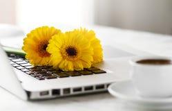 L'espace de fonctionnement ou lieu de travail avec l'ordinateur portable, les fleurs et le café o Photos stock