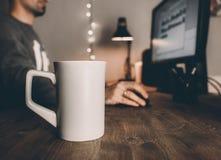 L'espace de travail à la maison dans le temps de soirée avec frappe, ordinateur et tasse de thé Temps confortable de soirée Images libres de droits