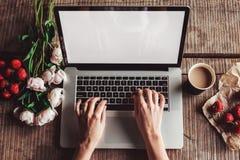 L'espace de travail avec des mains du ` s de fille, l'ordinateur portable, bouquet des pivoines fleurit, café, les fraises, smart Image libre de droits